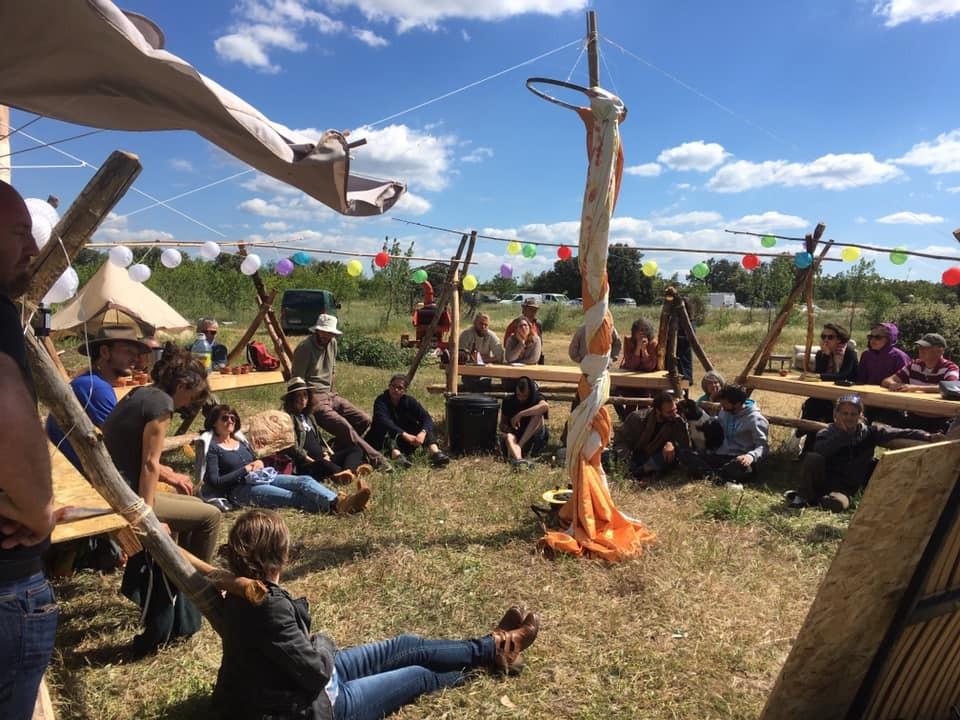 groupe de personnes assises en cercle autour d'une structure en bois, pendant une animation de groupe